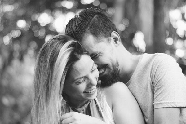 casal sorrindo juntos abraçados